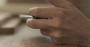 Young man hands using smartphone sitting at the table closeup Stock Photography