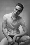 Young man handsome posing, strong jawline. One young adult man model posing, strong jawline, black and white image stock photography