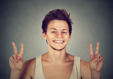 Young man, handsome student holding up peace victory, two sign Stock Images