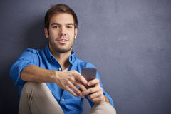 Young man with handy. Close-up shot of a young handsome man using his cellphone and texting message while sitting by the wall Stock Photography