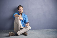 Young man with handy. Full length shot of a young man using her cellphone while browsing on the social media Royalty Free Stock Photos