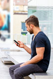 Young man on handy. Young, modern man with smart phone Royalty Free Stock Images