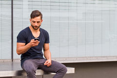 Young man on handy. Young, modern man with smart phone Stock Photo