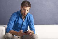 Young man with handy. Shot of a young handsome man using his cellphone and texting message while sitting on the sofa by the wall Royalty Free Stock Photography