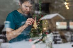 Young man hanging wooden tree on a Christmas tree Stock Photography
