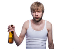 Young man with hangover holding beer bottle. After party Royalty Free Stock Photos
