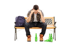 Young man with hangover sitting on a bench, Royalty Free Stock Images