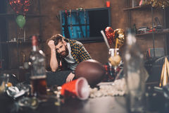 Young man with hangover sitting on couch in messy room after party Stock Photos
