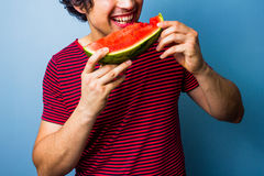 Young man happily eating watermelon Royalty Free Stock Photography