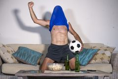 Young man happy and excited watching football match on TV celebrating victory goal crazy with team jersey over his head in fan con. Young attractive man happy Royalty Free Stock Photo