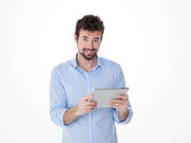 Young man happy for his new technologic present. One guy holding and using one grey tablet Stock Photo
