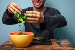 Young man is a happy salad tosser Royalty Free Stock Photography