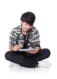 Young man happy using tablet pc. Young student man happy using tablet pc and sitting on floor in full length isolated on white background, asian people Stock Images