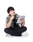 Young man happy using tablet pc. Young student man happy using tablet pc and look to copy space and sitting on floor in full length isolated on white background Stock Photography