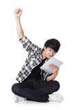 Young man happy using tablet pc. Young student man happy using tablet pc and sitting on floor in full length isolated on white background, asian people Stock Photos