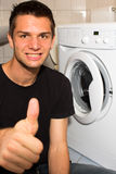 Young man happy with washing mashine. And doing thumb up Stock Photography