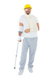 Young man in hard hat with broken hand and crutch Royalty Free Stock Image