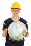 Young man in hard hat holding globe Stock Photo
