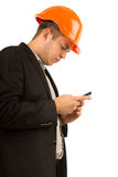 Young man in a hardhat reading a text message. Young man in a hardhat and suit standing reading a text message on his mobile phone with a serious expression Stock Photo