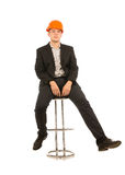 Young man in a hardhat sitting on a bar stool Stock Image