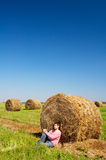 Young man on the harvested field. With straw bales Royalty Free Stock Image