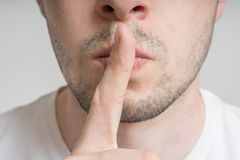 Young man has finger on lips and showing be quiet gesture Stock Photo