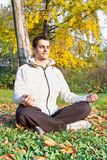 Young man has meditating in park Stock Images
