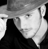 Young Man in Hat. College-age man with tipping his hat. Black background and focus on his eyes stock photos