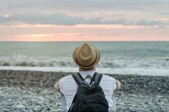 Young man in hat and with backpack sitting on the beach against the backdrop of the sea and sunset sky. Back view Royalty Free Stock Photography