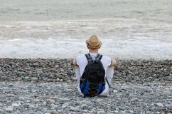 Young man in a hat and with a backpack is sitting on the beach on the background of the sea. View from the back Stock Images