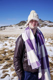 Young man with hat and blanket traveling in the winter mountain. Young man traveling and freezing in the cold  winter mountain Stock Photos
