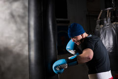 Young man in a hat and boxing gloves training with boxing punchi Stock Image