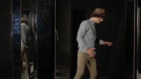 Young man dancing in a hat. Young man in a hat and casual clothes dancing indoors among mirrors. The guy shows dance moves and is reflected in the mirrors. The stock video