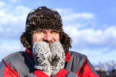 Young man with hat and coat shivering from cold. In winter Stock Image
