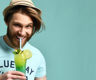 Young man in hat drinking margarita cocktail drink juice happy looking at camera. Over blue mint background royalty free stock image