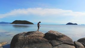 Young man in hat enjoys freedom at seaside view walks on stones. View from drone flying to the sea. 1920x1080. Hd stock video footage