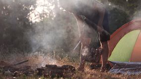 A young man is grilling meat on a fire in the forest. stock video footage