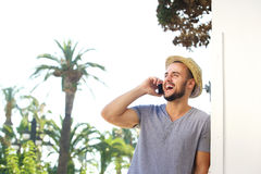 Young man with hat listening to mobile phone and laughing Stock Images
