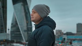 Young man in a hat looking far away against the background of skyscrapers stock footage