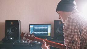 Young man in hat musician composes and records soundtrack playing the guitar using computer, headphones and keyboard. Focus on equipment Royalty Free Stock Photo