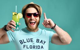 Young man in hat and red sunglasses hold margarita cocktail drink juice happy cheers pointing finger up over blue Royalty Free Stock Images