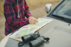 Young man in hat with road map and binoculars searching the correct road f royalty free stock photo