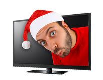 Young man with hat of Santa Claus comes out from the TV. Royalty Free Stock Image