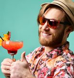 Young man in hat show thumb up drinking red margarita cocktail drink juice happy looking at camera over blue Royalty Free Stock Image