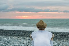 Young man in hat sitting on the beach against the backdrop of the sea and sunset sky. Back view Stock Photos