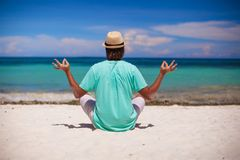Young man in hat sitting in the lotus position on Royalty Free Stock Photo