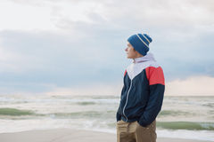 Young man in a hat standing by the sea and looks into the distance Royalty Free Stock Images
