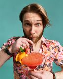 Young man in hat and sunglasses drinking margarita cocktail drink juice happy looking at camera laughing over light green. Background royalty free stock image