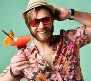 Young man in hat and sunglasses drinking margarita cocktail drink juice happy looking at camera laughing over light green Stock Images