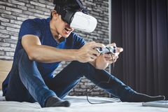 Young man have fun on bedroom in virtual reality headset or 3d g. Lasses playing video game, gaming and technology concept royalty free stock image